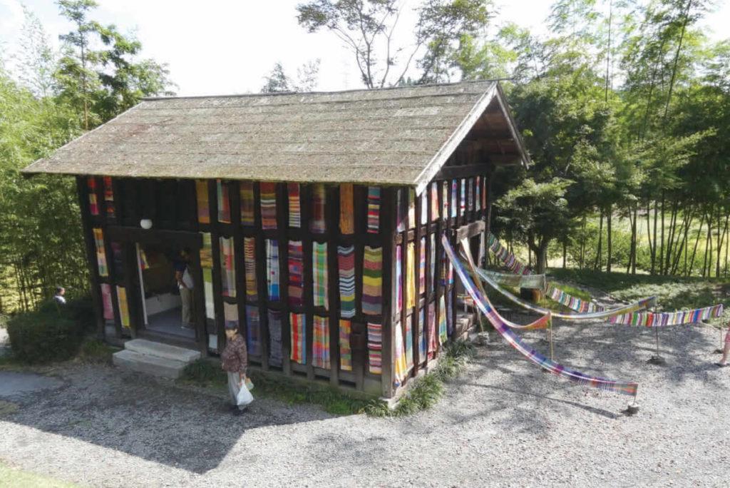 風の沢ミュージアムのギャラリー「ハナレ」の外観写真。黒っぽい木造平屋でイベント用に手織り布で飾り付けされている